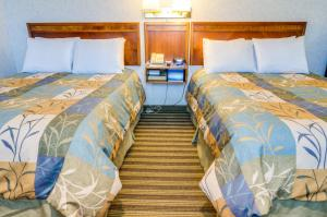 A bed or beds in a room at Francisco Bay Inn
