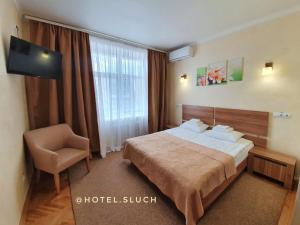 A bed or beds in a room at Hotel Sluch