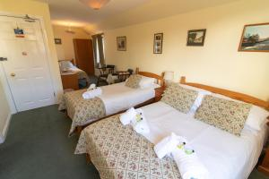 A bed or beds in a room at Auld Cross Keys Inn
