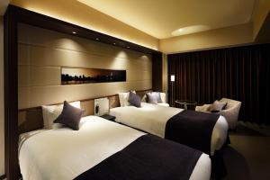 A bed or beds in a room at Solaria Nishitetsu Hotel Ginza