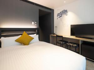 A bed or beds in a room at Hotel Intergate Osaka Umeda