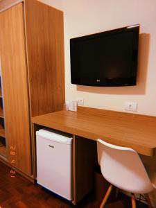 Uma TV ou centro de entretenimento em Hotel Amália