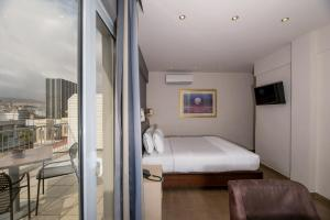 A bed or beds in a room at Piraeus City Hotel
