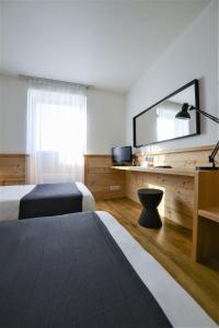 Un ou plusieurs lits dans un hébergement de l'établissement Golf Hôtel Grenoble Charmeil