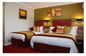A bed or beds in a room at Ballymac Hotel