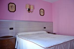 A bed or beds in a room at Hostal La Corte