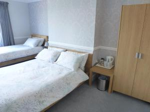 A bed or beds in a room at Orrell Park Hotel