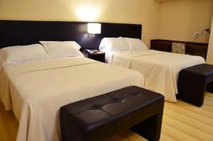 A bed or beds in a room at Le Parc Hotel & Suite