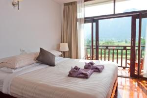 A bed or beds in a room at Silver Naga Hotel