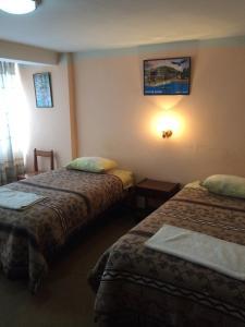 Кровать или кровати в номере Hostal Los Pinos Inn