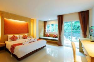 Кровать или кровати в номере Sungthong Kamala Beach Resort