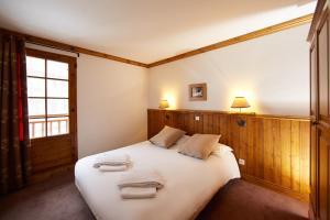 A bed or beds in a room at CGH Résidences & Spas les Chalets du Soleil Authentiques