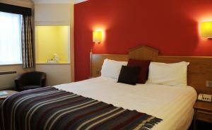 A bed or beds in a room at Village Hotel Liverpool