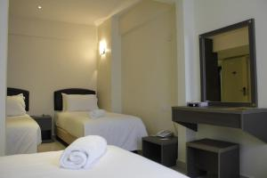 A bed or beds in a room at SunGold Inn Sdn Bhd