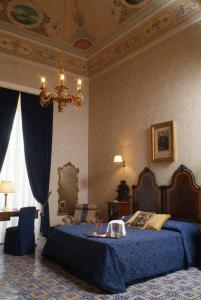 A bed or beds in a room at Palazzo Failla Hotel