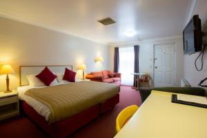 A bed or beds in a room at Club Motel Armidale