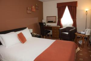 A bed or beds in a room at Best Western Wakefield Hotel St Pierre