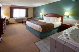 A bed or beds in a room at AmericInn by Wyndham Chippewa Falls