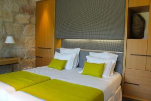 A bed or beds in a room at Lousada Country Hotel