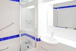 A bathroom at ibis Budget Warrington Lymm Services