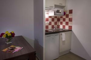 A kitchen or kitchenette at Vacancéole - Résidence Le Clos du Rocher