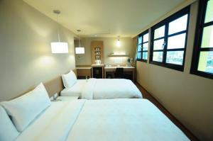 A bed or beds in a room at Kindness Hotel - Kaohsiung Main Station