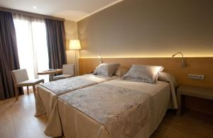 A bed or beds in a room at M.A. Hotel Sevilla Congresos