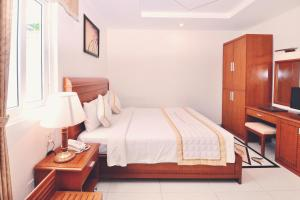 A bed or beds in a room at Tan Hoang Long Hotel
