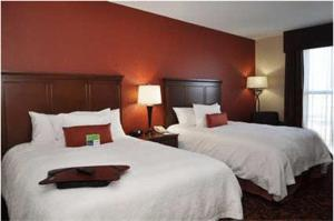 A bed or beds in a room at Hampton Inn by Hilton Edmonton South