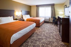 A bed or beds in a room at AmericInn by Wyndham Blue Earth