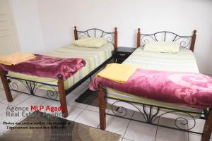 A bed or beds in a room at Résidence Assoulil MLP