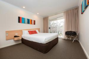 A bed or beds in a room at Ramada Encore Belconnen Canberra
