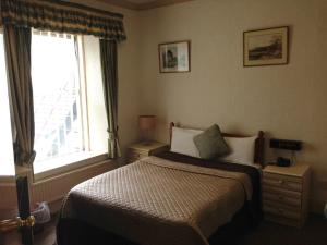 A bed or beds in a room at Tregenna Hotel