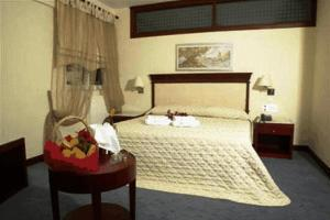 A bed or beds in a room at Crithoni's Paradise Hotel