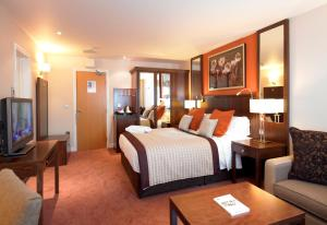 A bed or beds in a room at Best Western Plus Milford Hotel