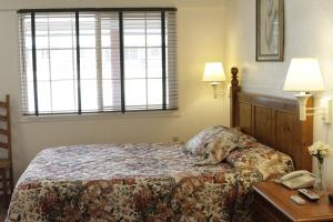A bed or beds in a room at Jumping Frog Motel
