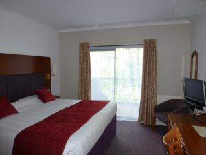A bed or beds in a room at Cross Roads By Greene King Inns