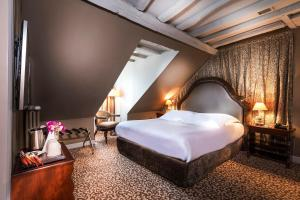 A bed or beds in a room at Hotel Odeon Saint-Germain