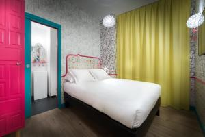 A bed or beds in a room at Hôtel Crayon Rouge by Elegancia