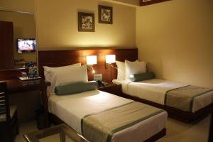 A bed or beds in a room at Hotel Green Olive