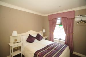 A bed or beds in a room at Germaines Hotel