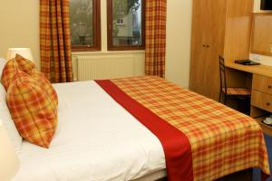 A bed or beds in a room at The Pipers' Tryst Hotel