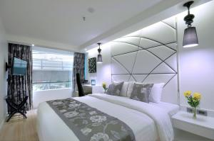 A bed or beds in a room at Sukhumvit Suites Hotel
