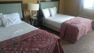 A bed or beds in a room at Branford Motel