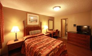 A bed or beds in a room at Executive Motel
