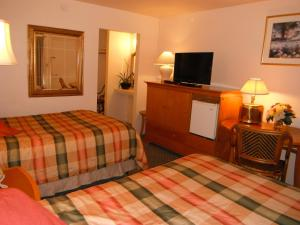 A bed or beds in a room at Colusa Riverside Inn