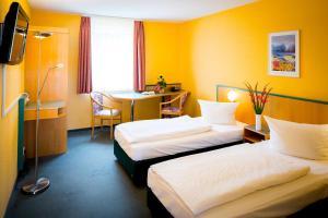 Ein Bett oder Betten in einem Zimmer der Unterkunft Apart Hotel Weimar