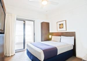 A bed or beds in a room at Cottesloe Beach Hotel