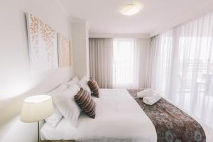 A bed or beds in a room at Newcastle Central Plaza Apartment Hotel