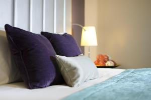 A bed or beds in a room at The Belgrave Hotel